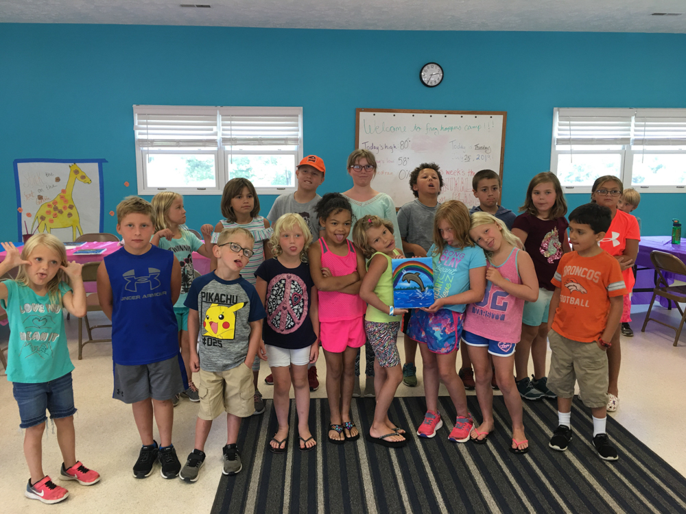 Frog Hoppers Summer Camp participants gather in the Activity Center to show off their artwork.