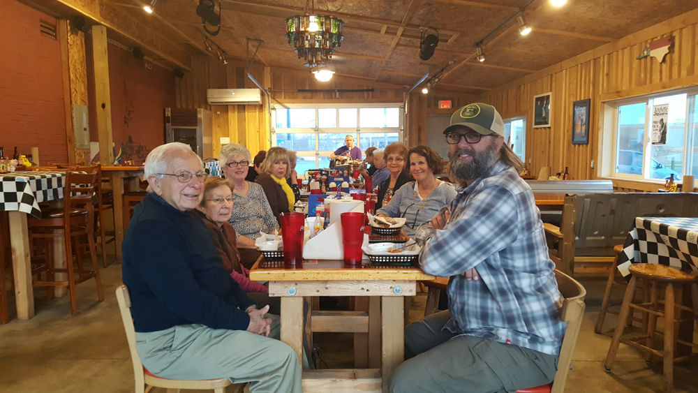 A group of seniors along with Parks and Rec staff gather around a table at Fatback Soul Shack on a trip to the RU Planetarium.